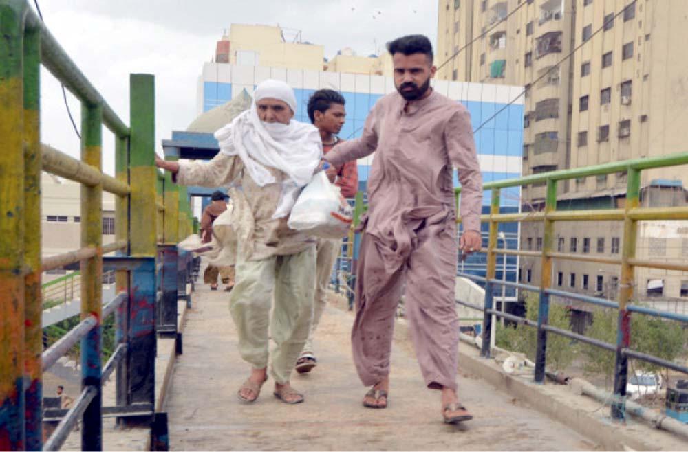 Man helps an elderly woman on a pedestrian bridge in Karachi on Tuesday. PHOTOS: EXPRESS/NNI