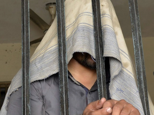 This photo taken on April 27, 2014 shows a handcuffed Pakistani suspect in connection with the murders of three homosexual men, standing in a lockup at a police station in Lahore. PHOTO: AFP