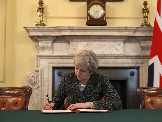 British Prime Minister Theresa May in the cabinet office signs the official letter to European Council President Donald Tusk invoking Article 50 and the United Kingdom's intention to leave the EU on March 28, 2017 in London, England. PHOTO: REUTERS