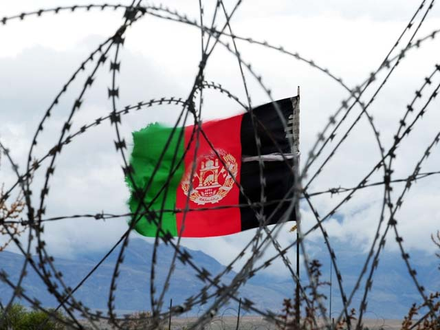 In this picture taken on March 17, 2014, the Afghan national flag flutters in the wind behind barbed wire at a forward operating base where soldiers attached to the 4th Brigade, 201 Army Corps of the ANA live in Khogyani district. PHOTO: GETTY