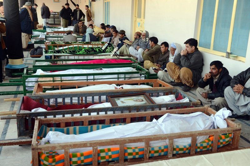 shia muslim mourners sit beside the coffins of blast victims at a mosque following overnight twin suicide bombings in quetta on january 11 2013 photo afp