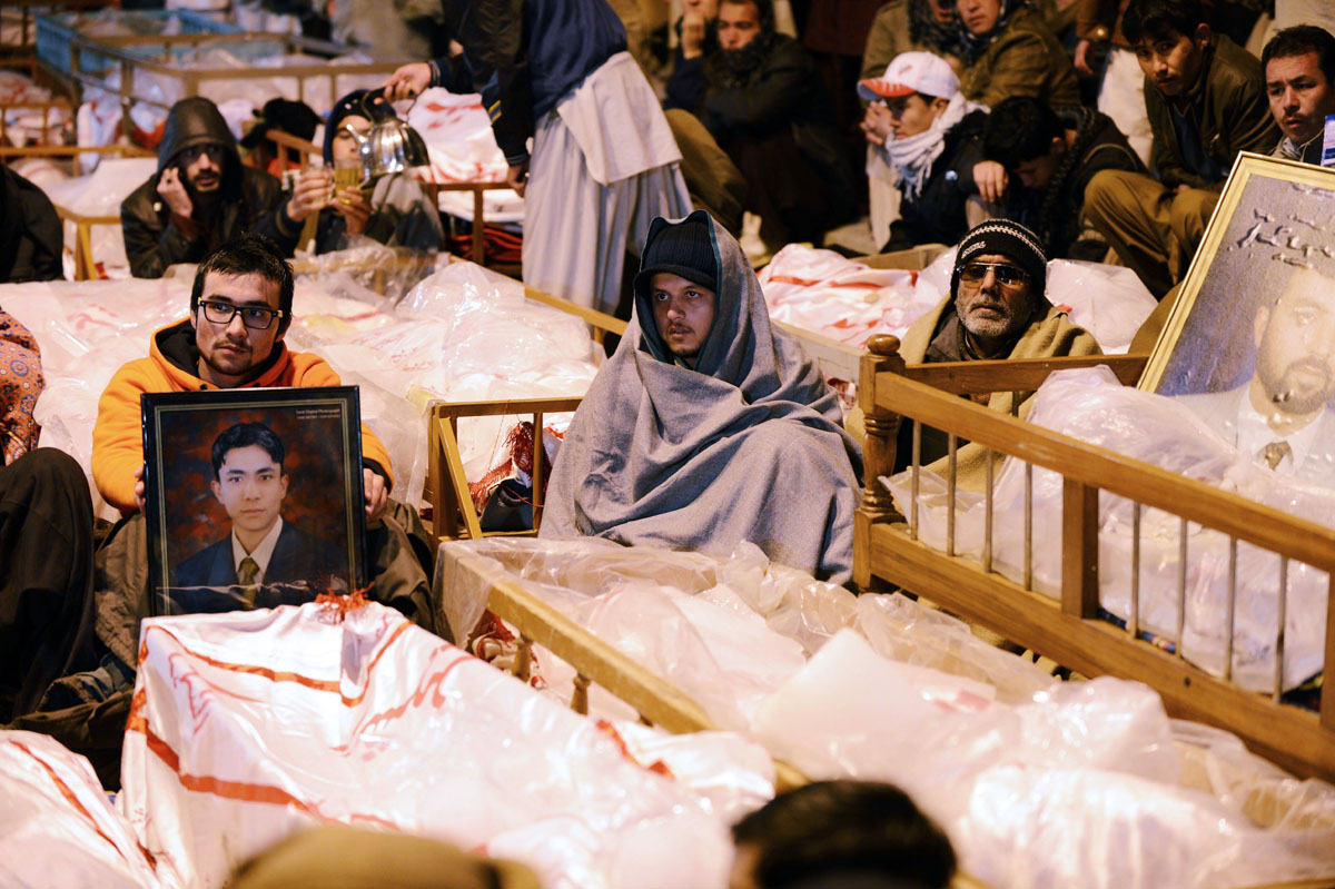 shia muslims demonstrate and sit amongst the coffins and portraits of bomb blast victims in quetta on january 12 2013 photo afp
