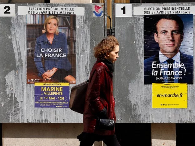A pedestrian walks past electoral posters of French presidential election candidate Emmanuel Macron and far-right Front National party Marine Le Pen on April 28, 2017 in Paris, France. PHOTO: GETTY