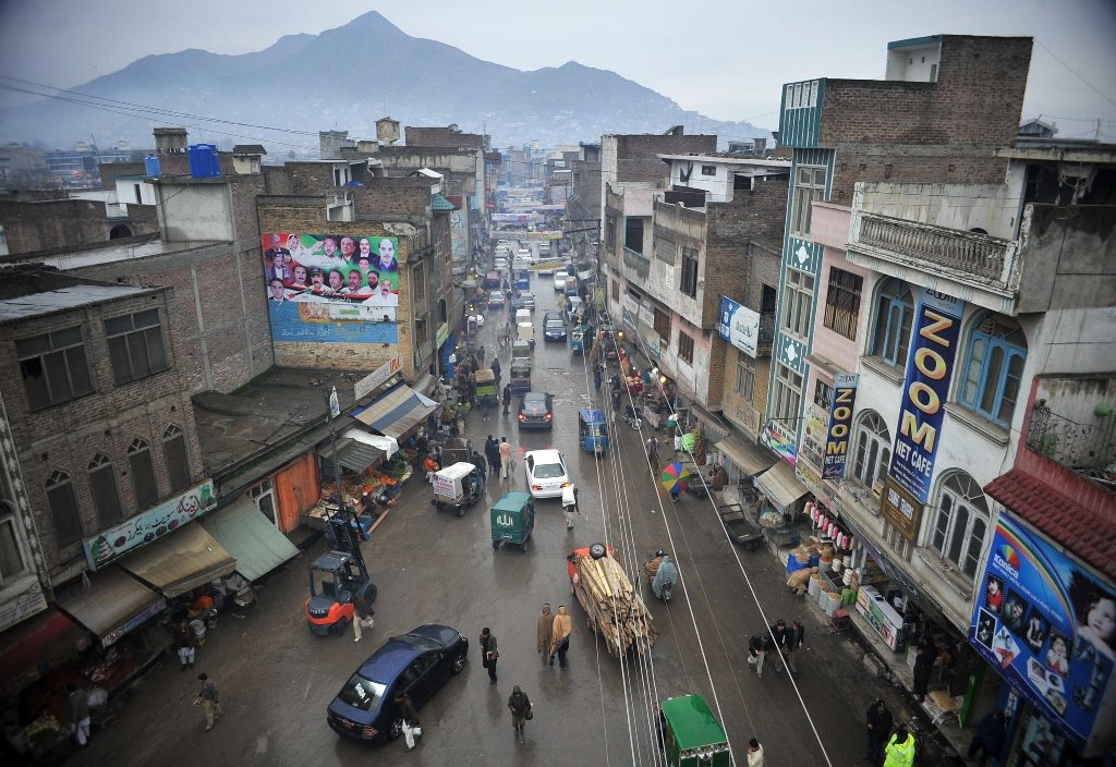 In this photograph taken on January 12, 2013,  Pakistani pedestrians and cars travel down a main street in Mingora, the main town of Swat Valley. PHOTO: AFP