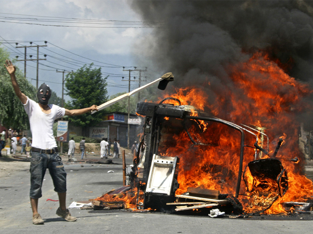 a masked kashmiri shouts anti indian slogans beside a burning police vehicle in pampore on sunday photo afp