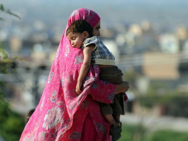 A Pakistani woman carries her son as she walk on a street in Islamabad on May 13, 2012, on Mother's Day. PHOTO: AFP