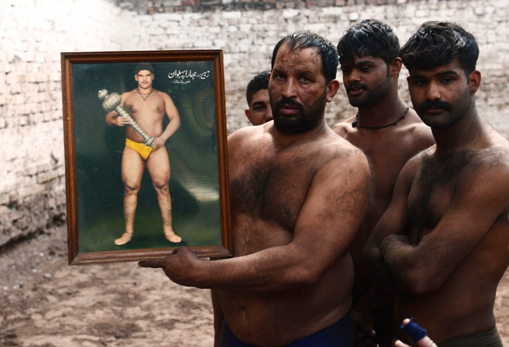 Wrestlers hold a  picture of a famous Jhara wrestler during training at a practise ring in Lahore. PHOTO: AFP