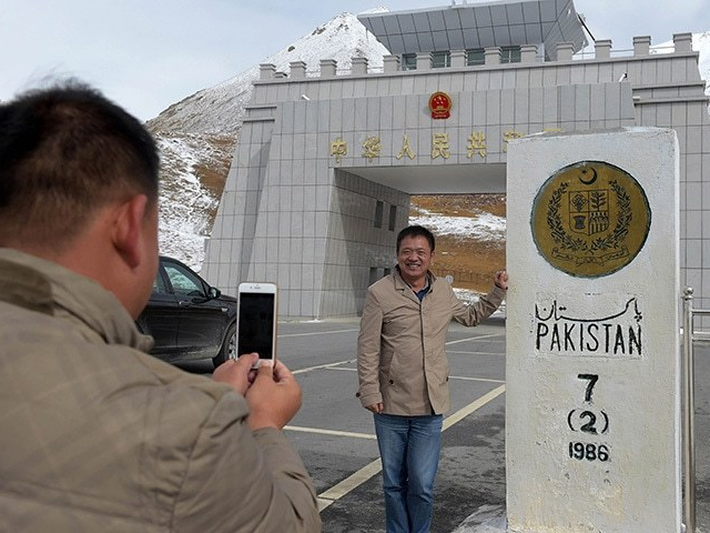 In this photograph taken on September 29, 2015, a Chinese national takes a photograph of his colleague at the Pak-China Khunjerab Pass, the world's highest paved border crossing at 4,600 metres above sea level. PHOTO: AFP