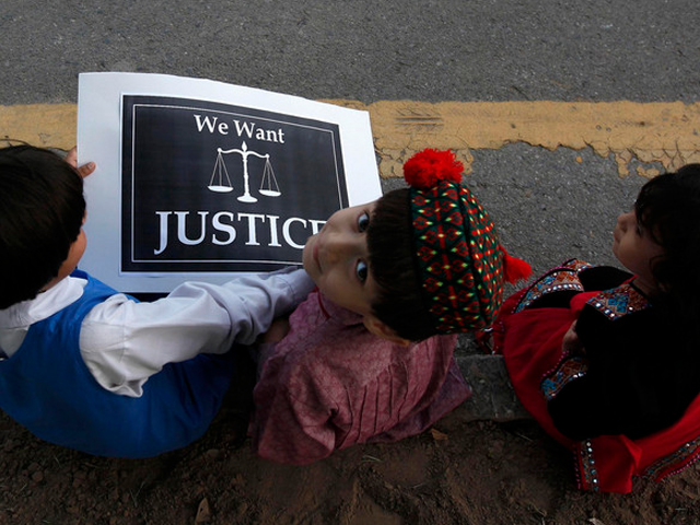 Children sit with a placard on a roadside during a protest by members of a civil society, against the rape of a five-year-old girl in Lahore. PHOTO: REUTERS