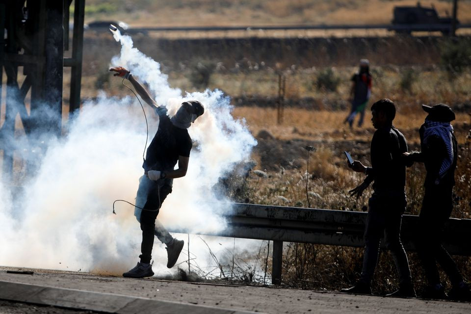 A Palestine protestor throws back a tear gas grenade during an anti-Israel protest over cross-border violence between Palestinian in Gaza and the Israeli military, near Hawara checkpoint near Nablus in the Israeli-occupied West Bank, May 18, 2021. PHOTO: REUTERS