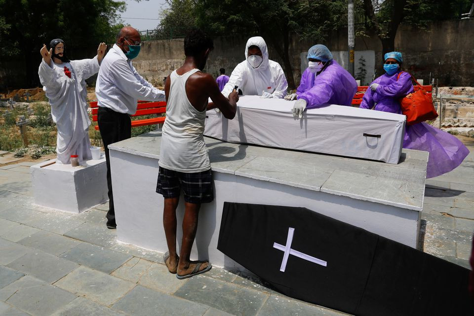 Relatives of a person who died from the coronavirus disease (COVID-19) close the coffin before the burial, at a graveyard in New Delhi, India, April 29, 2021. REUTERS