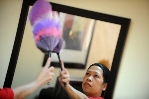 a filipina maid cleans a mirror during a government mandated crash course in domestic duties in manila on september 14 2011 photo afp file