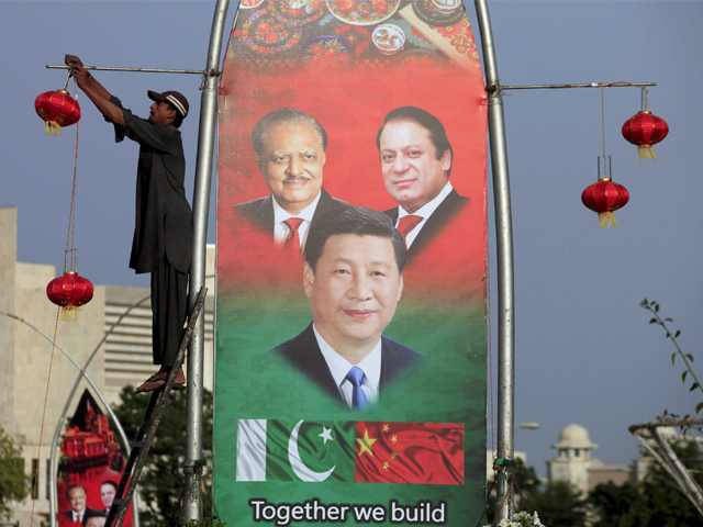 A man hangs decorations next to a banner showing Pakistan's President Mamnoon Hussain (L), Chinese President Xi Jinping (C) and Pakistan's Prime Minister Nawaz Sharif, before Xi's visit to Islamabad April 19, 2015. PHOTO: REUTERS