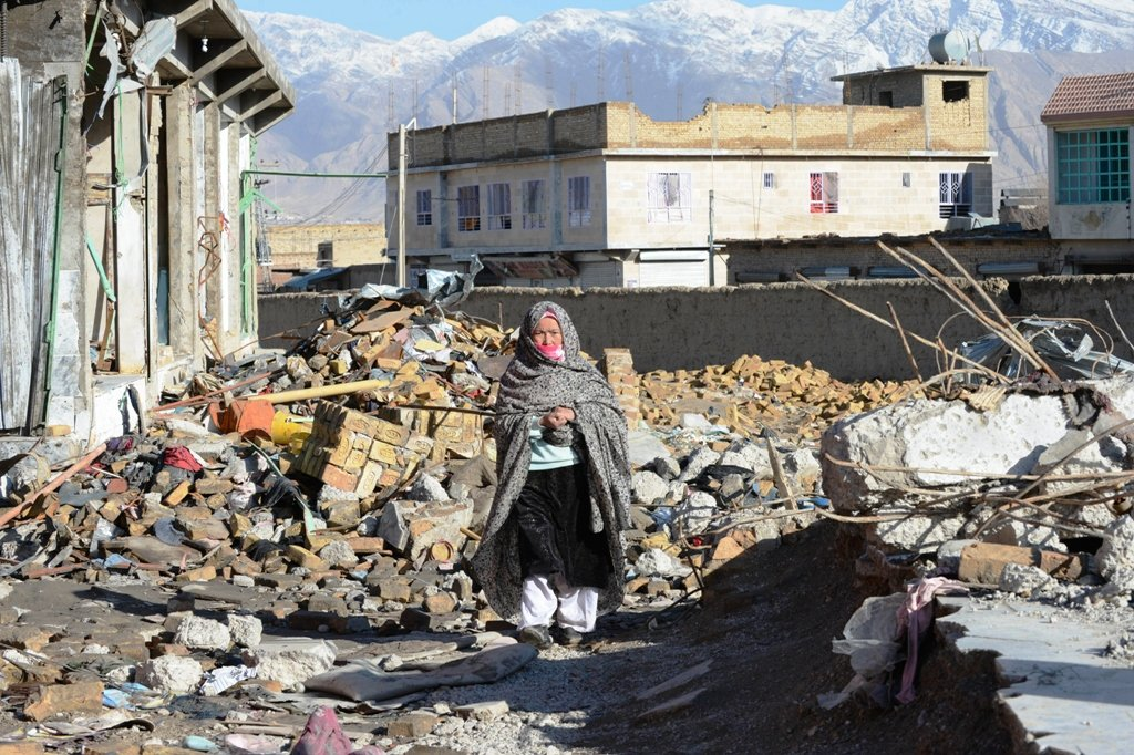 a pakistani hazara resident walking through debris from a bombing on february 16 which killed 89 shia muslims in quetta photo afp