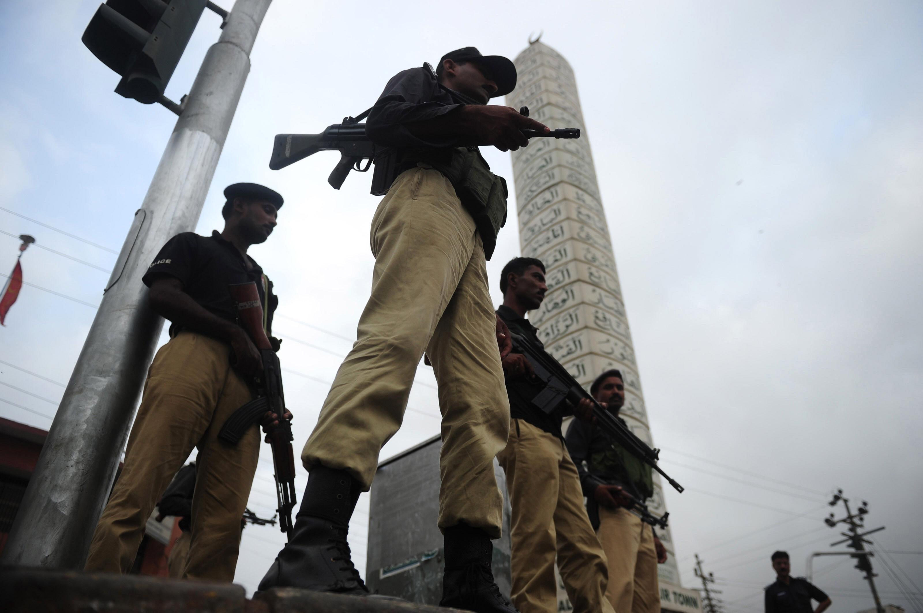Pakistani policemen stand guard in a troubled neighbourhood in Karachi. PHOTO: AFP