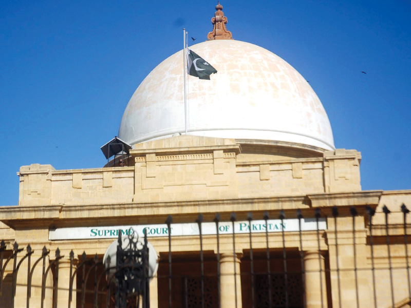 the flag flies at half mast at the supreme court registry in karachi following two bomb blasts at abbas town courts below wore a deserted look as lawyers boycotted all legal proceedings on monday photo ppi express