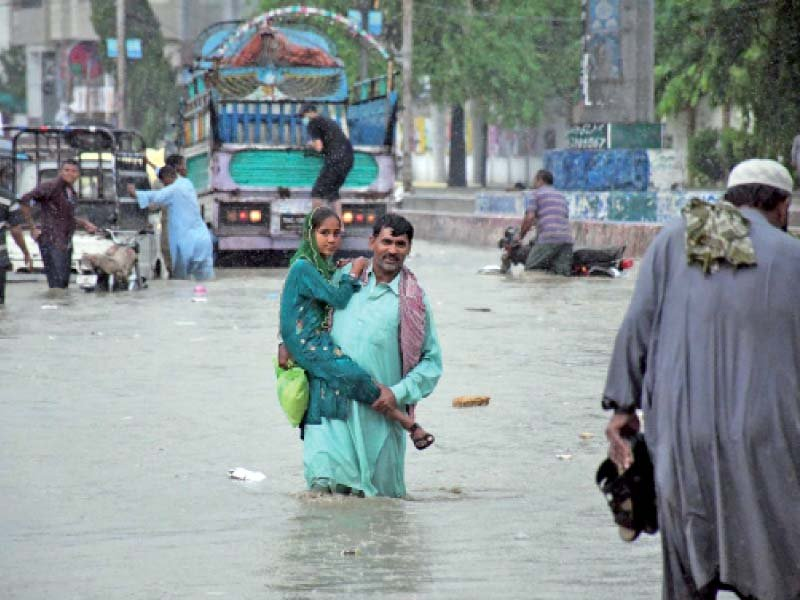 a man carrying his daughter wades through a flooded street in karachi as rain lashed the metropolis for the second consecu tive day on friday photo online
