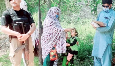 A policeman stands guard as health department workers administer polio drops to children during the inoculation drive in Swabi district. PHOTO: EXPRESS