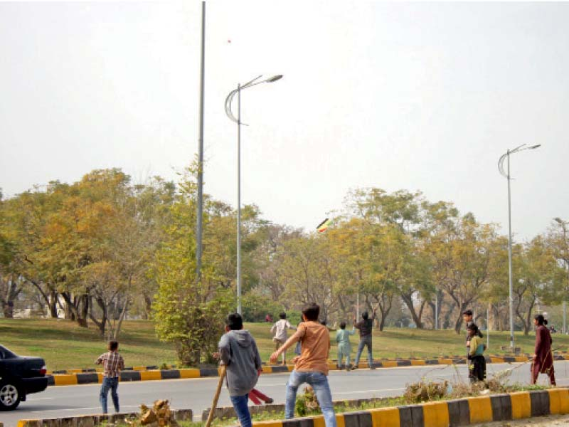 youngsters run after a falling kite on the busy 7th avenue in the federal capital on wednesday a 13 year old boy was injured after he fell from his roof while flying a kite in rawalpindi photo online