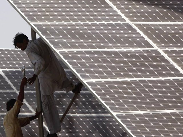 Technicians work on solar panels in a power station at Hub about 25 km (15 miles) from Karachi on June 18, 2010. PHOTO: REUTERS
