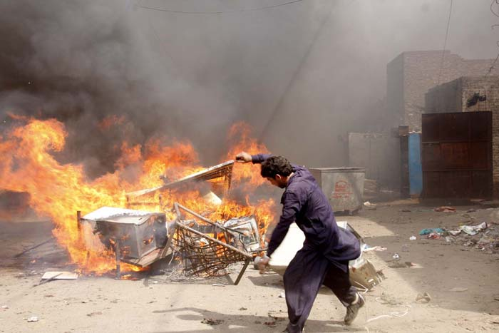A protester burns belongings from Christian houses in Lahore on Saturday. PHOTO: ABID NAWAZ/ EXPRESS