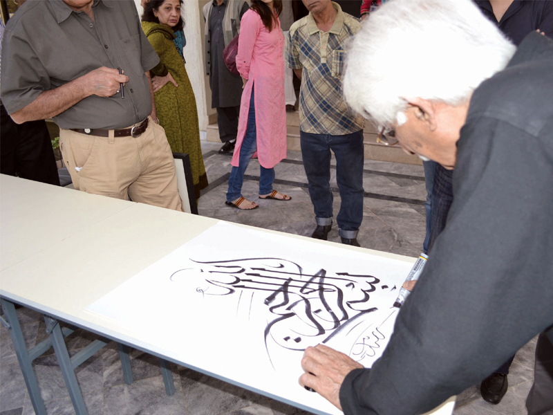 a painting by shehzad mughal left and an artist explaining her work to the audience at the fair on sunday noted calligrapher rasheed butt doing calligraphy photo express