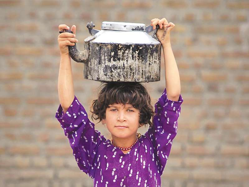 A girl, displaced by the 2010 heavy floods, carries a pot of water which she filled from a hand pump in Nowshera. PHOTO: FILE