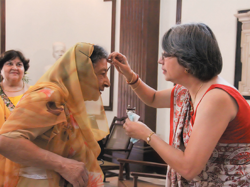 the principal of the school furengeez tampal puts a tilak on dr bn mama the chairperson of the school s management committee photo ayesha mir express