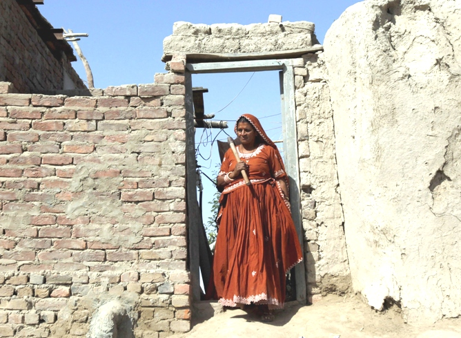 Veero Kolhi,a freed bonded labourer turned election candidate, carries a digger on her shoulder as she walks out of her home to work in field  on the outskirts of the city of  Hyderabad in Pakistan's Sindh province. PHOTO: REUTERS