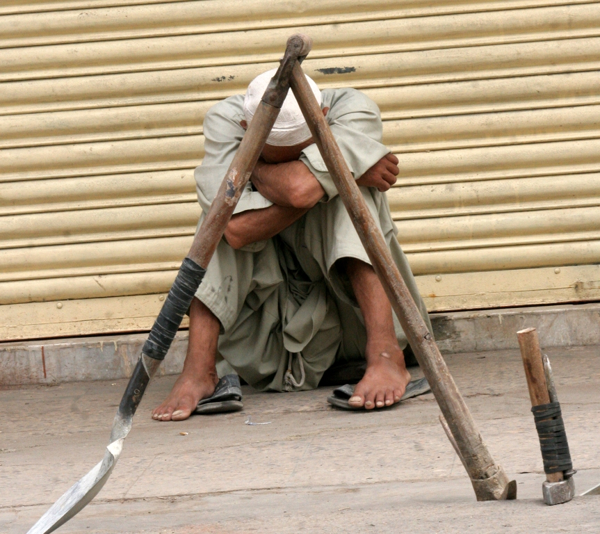 A labourer sits beside closed shops in Karachi during a strike on Wednesday. PHOTO: ATHAR KHAN/ EXPRESS