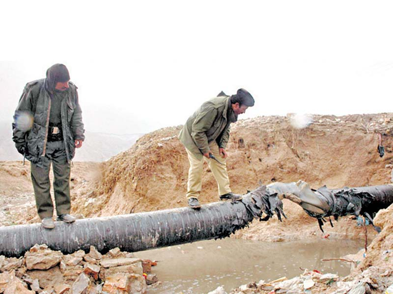 This file photo shows two security officials inspecting a section of a gas pipeline blown up by militants in Balochistan.