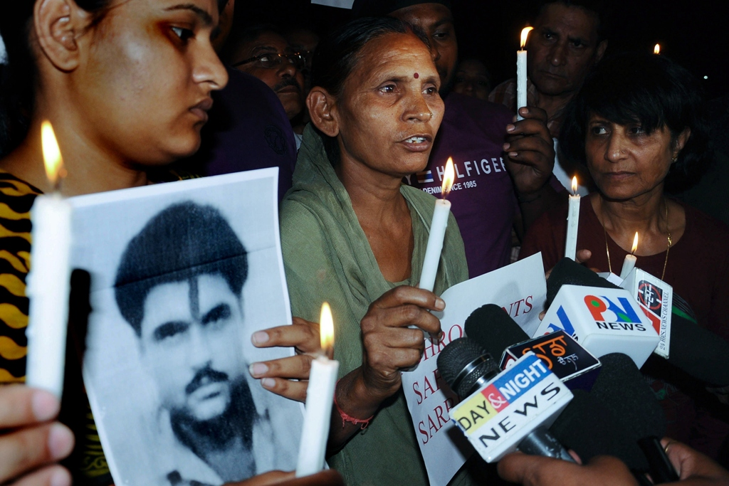 Sukhpreet Kaur (C), wife of Indian death row prisoner in Pakistan, Sarabjit Singh and Singh's daughter Swapandip (L), along with members of the Akhil Bhartiya Human Rights organisation (ABHRO), hold a candlelight vigil for the good health of Sarabjit Singh in Amritsar on April 27, 2013. PHOTO: AFP