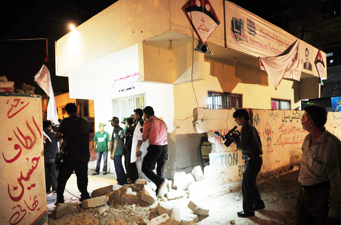Media officials record video the site of twin bomb blasts near the Muttahida Qaumi Movement (MQM) party office in Karachi on May 4, 2013. PHOTO: AFP
