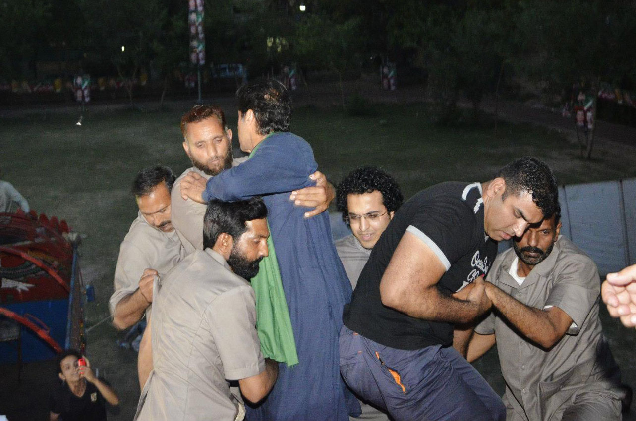 imran khan in blue falls as guards and supporters try to climb aboard the lift he is standing on photo pti social media