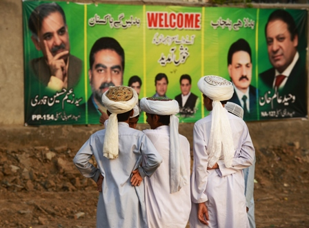 Young supporters of the PMLN stand near political posters during a political rally in Lahore May 9, 2013. PHOTOS: AFP