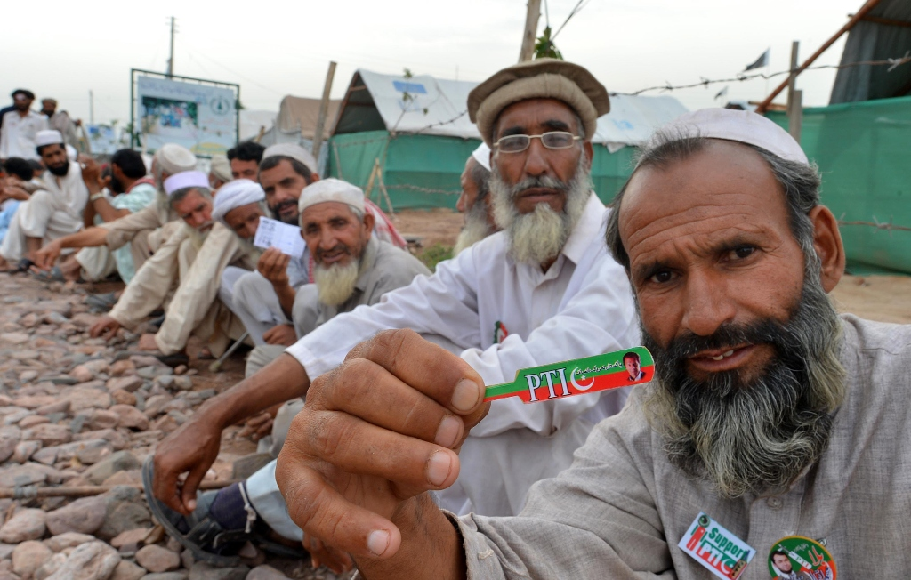 A PTI supporter sits in a queue waiting for his turn to cast vote outside a polling station in Jalozai camp. PHOTO: AFP