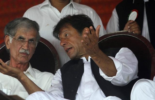 PTI chief Imran Khan talks with party leader Pervaiz Khattak. PHOTO: REUTERS/FILE