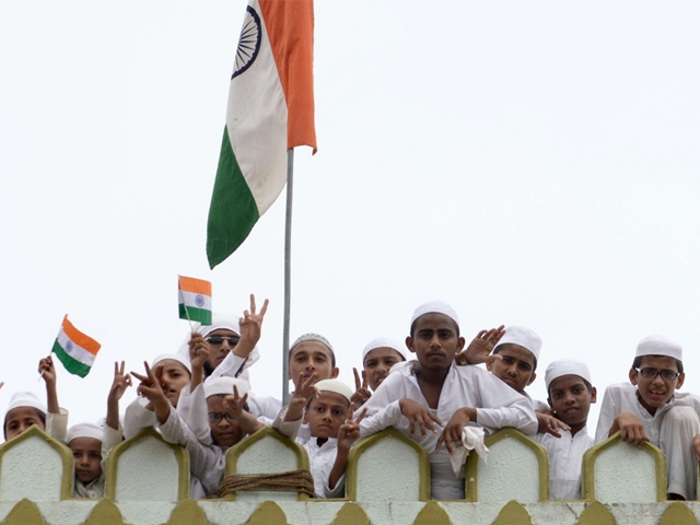 Indian Muslims celebrate Independence Day with national flags on the terrace of the Madrasa Arabia Islamia in the Juhapura area of Ahmedabad on August 15, 2015. PHOTO: AFP