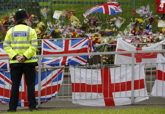 a police officer stands next to floral tributes flags and balloons left for british soldier lee rigby near the scene where he was killed in woolwich southeast london may 28 2013 photo reuters