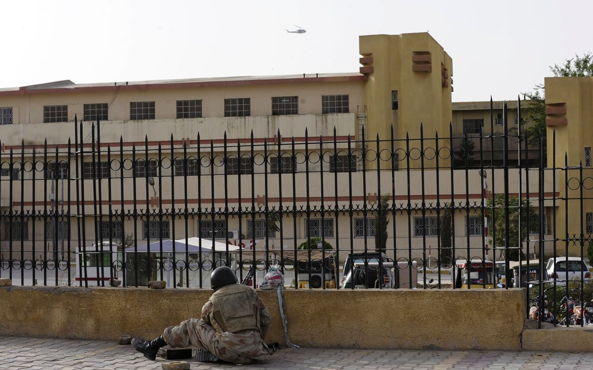 a paramilitary soldier takes up position outside the bolan medical complex as a helicopter circles above photo afp