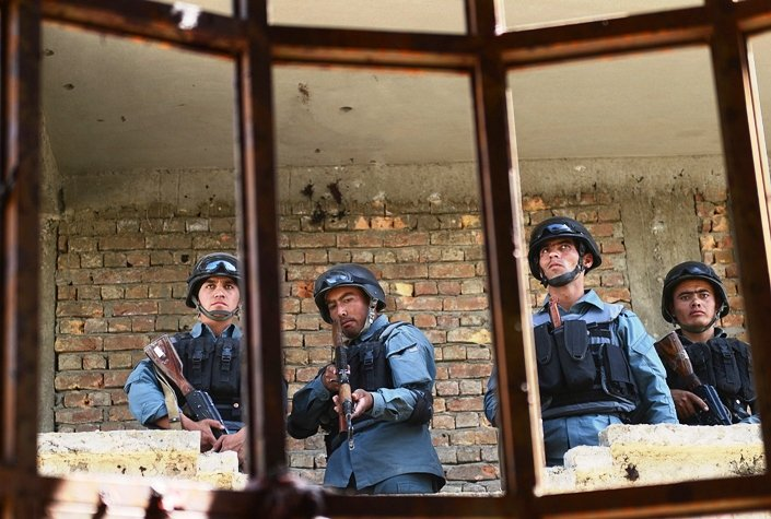 Afghanistan policemen stand guard in a building which was used for an attack.  PHOTO: AFP/FILE