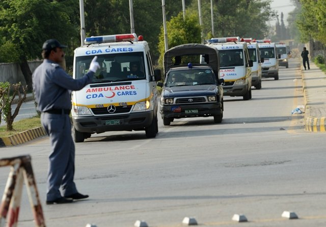 Pakistani police escort ambulances carrying the coffins of foreign tourists as they come out from Chaklala air base in Rawalpindi on June 23, 2013. PHOTO: AFP