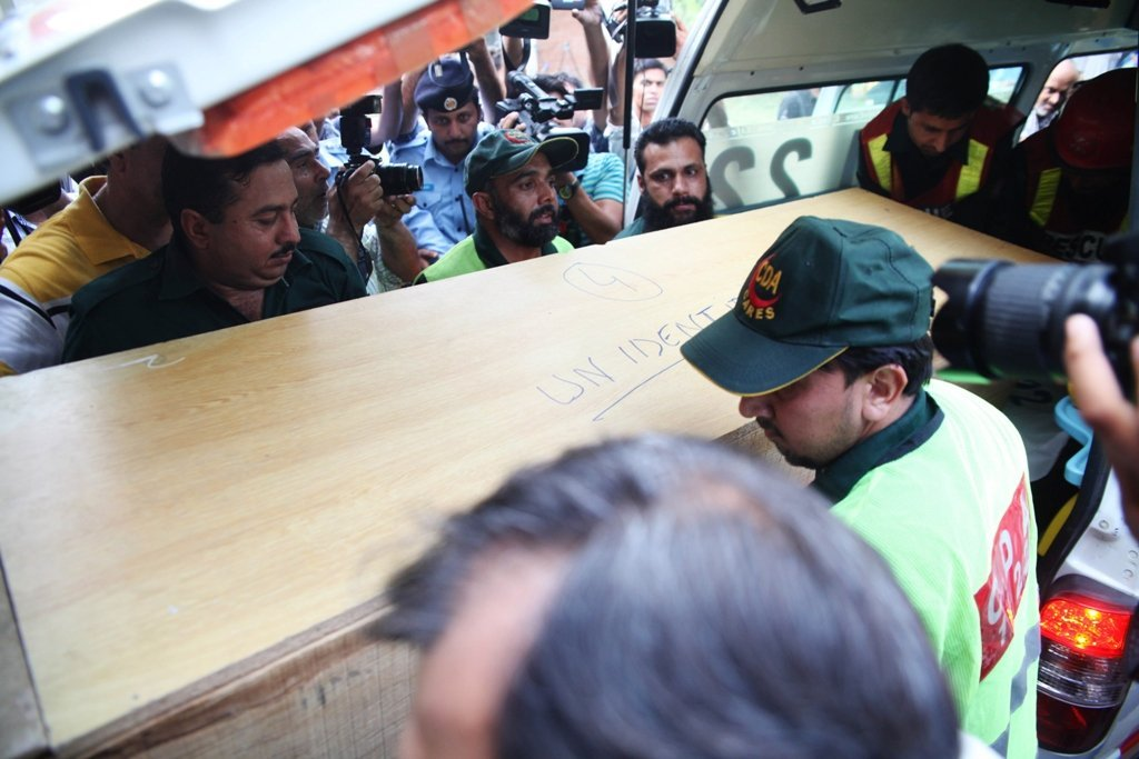 rescuers shift a coffin of a foreign tourist from an ambulance to a hospital in islamabad on june 23 2013 photo afp