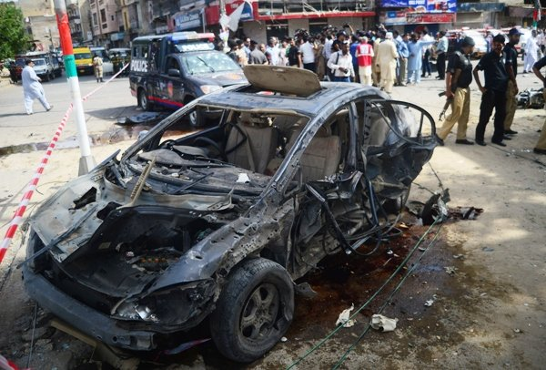 Security personnel gather around the car of Maqbool Baqir, a senior judge that was injured in a bomb attack in Karachi on June 26, 2013.  PHOTO: AFP