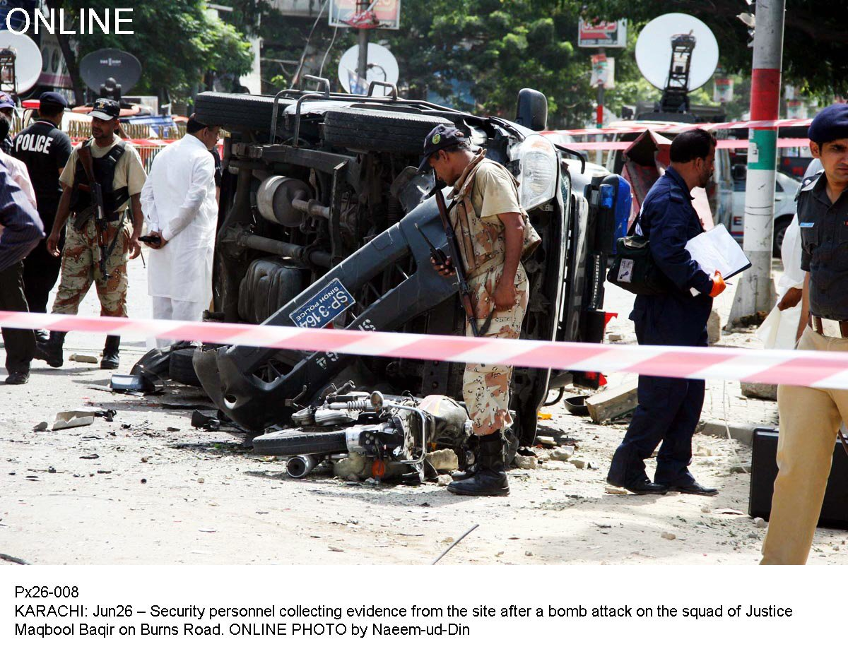 Officials inspect the aftermath of a bomb attack on a Sindh High Court Judge in Karachi. PHOTO: ONLINE