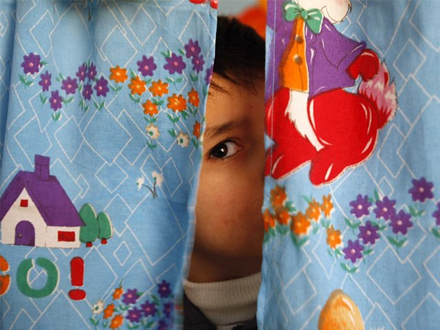 n autistic child peers from between curtains at the Consulting Centre for Autism in Amman, Jordan. PHOTO: REUTERS