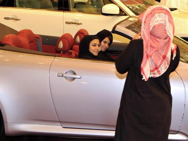 a saudi man takes a picture of two women sitting in a car at an auto show in jeddah photo afp