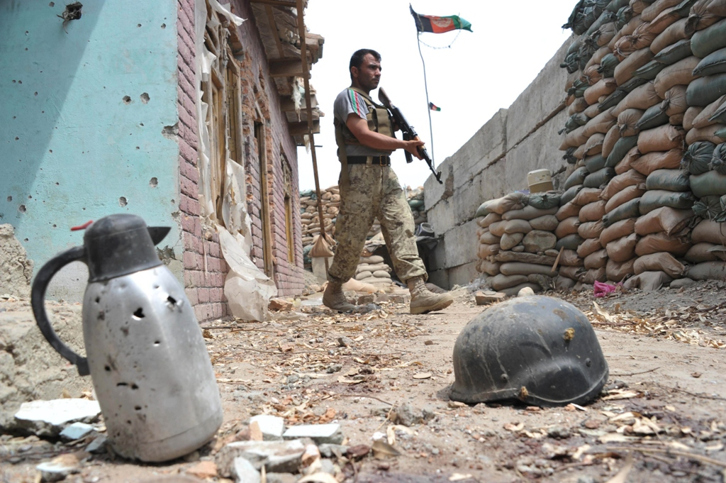 an afghan security serviceman keep watch at a damaged police post following an airstrike in bati kot district in nangarhar province on august 1 2013 photo afp