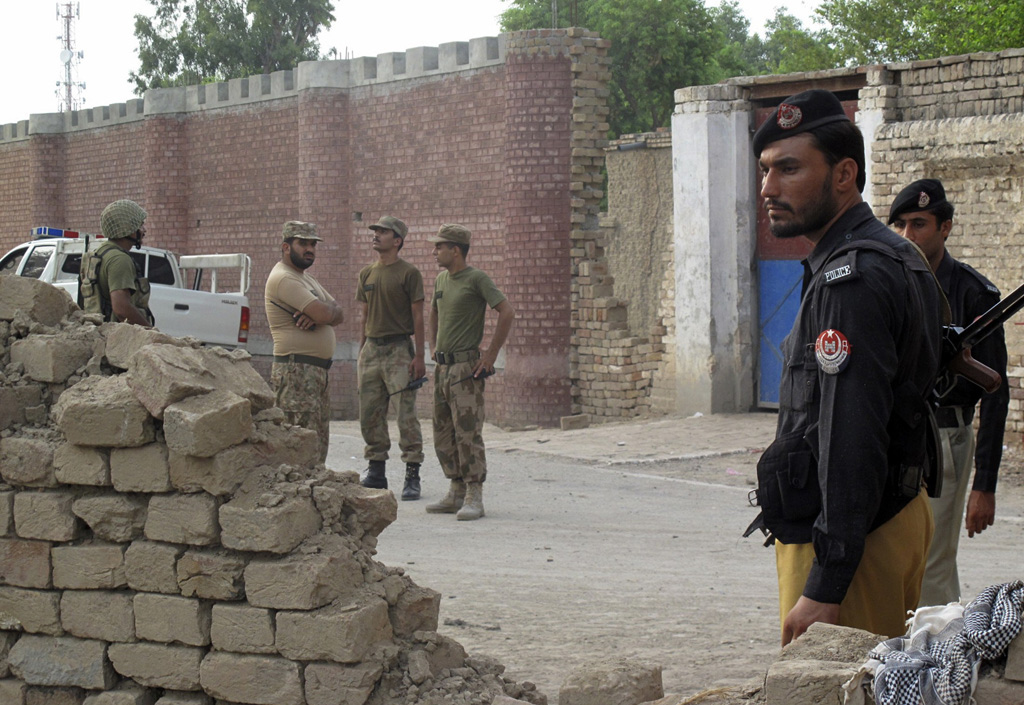 policemen r and ranger soldiers l stand outside a prison following a taliban attack in dera ismail khan july 30 2013 photo reuters
