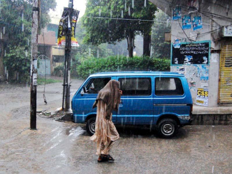 a man covers his head while walking amid heavy rain in islamabad photo muhammad javaid express